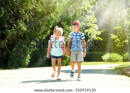 Happy active children with bags outdoors - stock photo