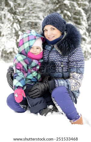 Happy active family having fun on winter snow outdoors. Smiling mother and daughter. - stock photo