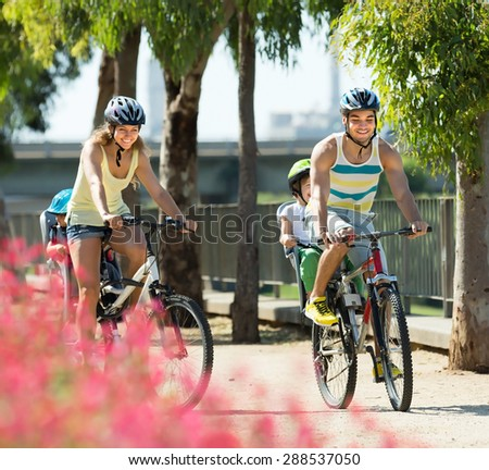 Happy active family of four cycling on street road in summer day