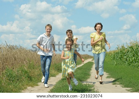 Happy active family running outdoors against the sky - stock photo