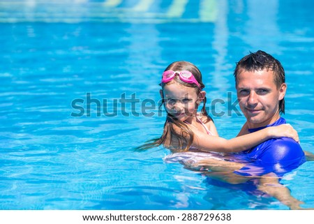Happy active family, young dad and little daughter playing in swimming pool enjoying summer vacation
