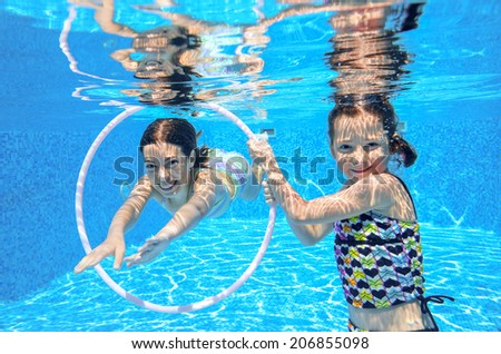 Happy active kids play underwater in swimming pool, girls diving and having fun, children on summer  vacation, sport concept  - stock photo