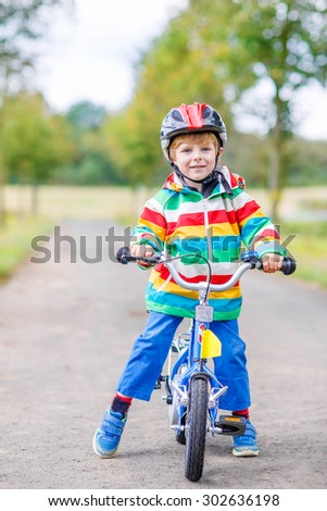 Happy active little boy having fun on bike on warm summer day. Countryside. Child in helmet. Active leisure and sports for kids.