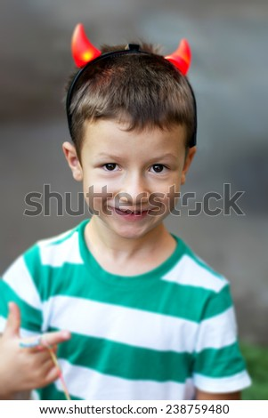 Happy active little boy with red glowing devil horns - stock photo