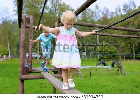 Happy active little child, blonde curly toddler girl wearing beautiful dress, having fun at playground in the park on sunny summer day - stock photo