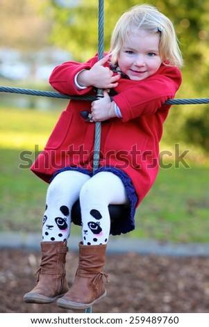 Happy active little child, blonde curly toddler girl wearing beautiful red coat, having fun playing at playground in city park on sunny spring day - stock photo