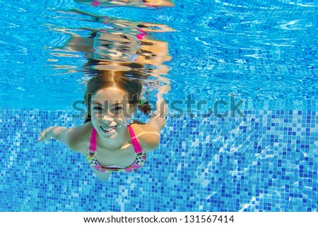 Happy active underwater child swims in pool, beautiful healthy girl swimming and having fun on family summer vacation, kids sport concept - stock photo