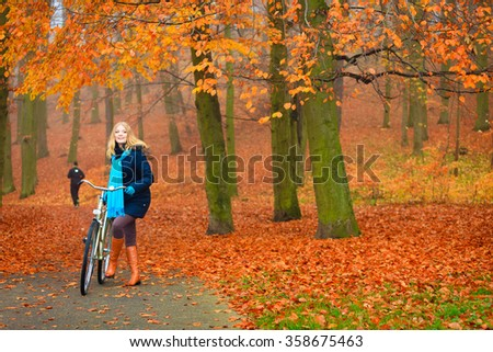Happy active woman girl riding bike bicycle relaxing in fall autumn park. Healthy lifestyle.
