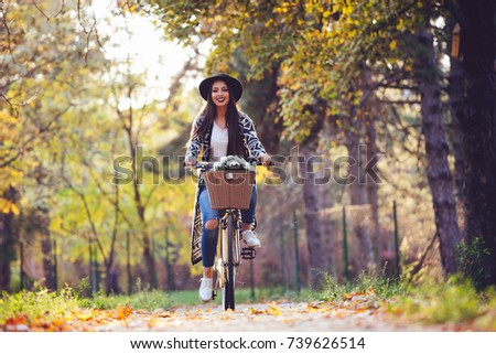 Happy active woman riding bike bicycle in fall autumn park