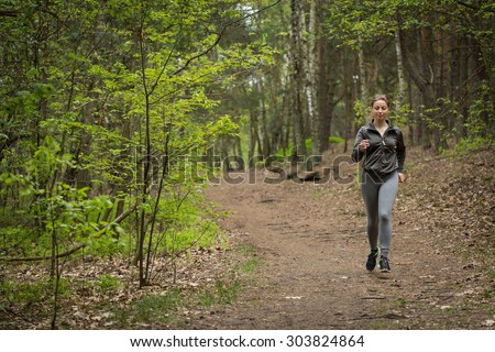 Happy active woman running on forest path