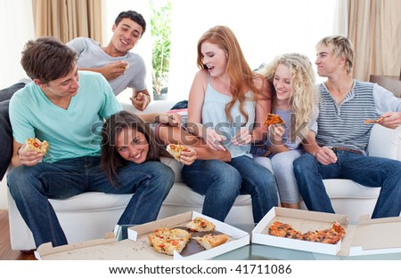 Happy adolescents eating pizza at home - stock photo
