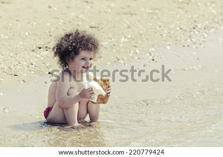 happy adorable child eating donut on beach and smiling - stock photo
