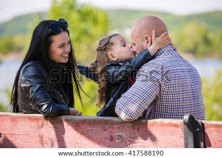 Happy adorable family on the bench in park: daughter kissing dad - stock photo