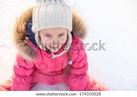 Happy adorable girl sitting on ice with skates after the fall - stock photo