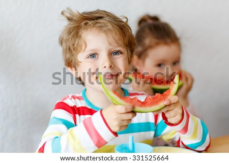 Happy adorable kid boy and little girl eating healthy food, fresh watermelon in kindergarten, nursery or at home. Fresh fruits as organic bio snack for children.
