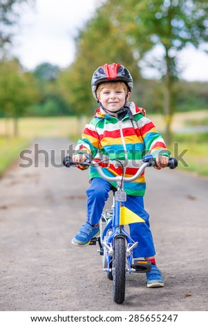 Happy adorable kid boy in safety helmet and colorful clothes on bike on summer day. Active leisure for children outdoors.