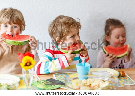 Happy adorable kid boys and little girl eating healthy food, fresh watermelon in kindergarten, nursery or at home. Fresh fruits as organic bio snack for children. Three kids.