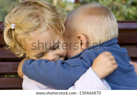 Happy adorable kids hugging each other - stock photo