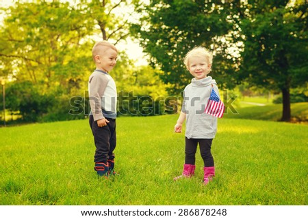 Happy adorable little blond Caucasian girl and boy smiling laughing holding hands and waving American flag outside  celebrating 4th july,  Independence Day, Flag Day concept - stock photo