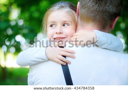 Happy adorable little girl hugging embracing her father - stock photo