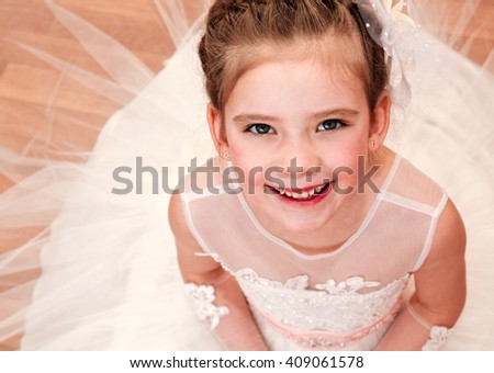 Happy adorable little girl in princess dress siitting on the floor