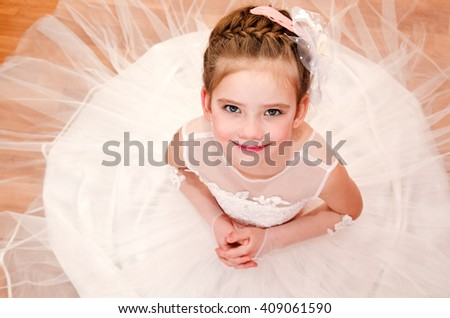 Happy adorable little girl in princess dress siitting on the floor - stock photo