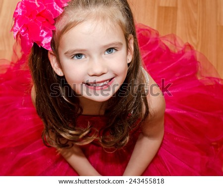 Happy adorable little girl in princess dress sitting on the floor - stock photo