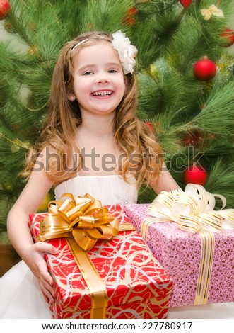 Happy adorable little girl with gift boxes near christmas tree