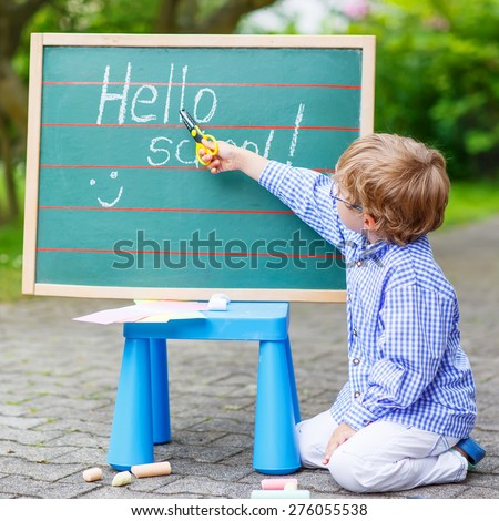 Happy adorable little kid boy with glasses at blackboard practicing writing, outdoor. school or nursery. Back to school concept - stock photo