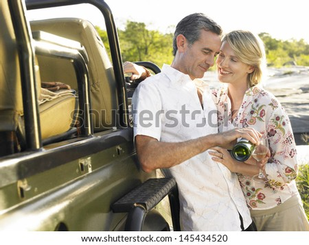 Happy adult couple by jeep with man pouring wine in glass - stock photo