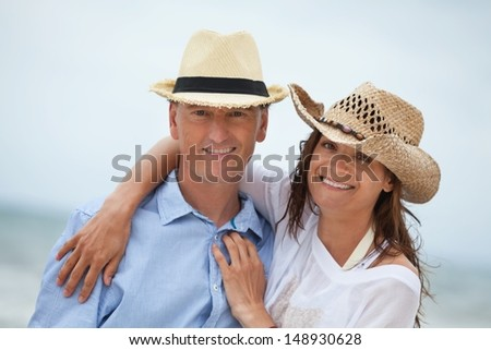 happy adult couple in summertime on beach having fun vacation - stock photo
