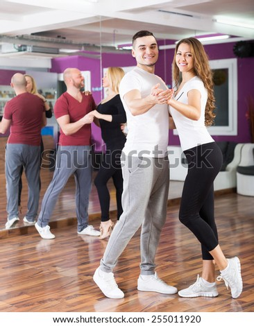 Happy adult couples enjoying of partner dance and smiling indoor - stock photo