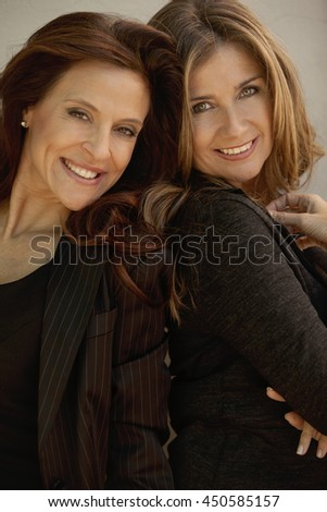 Happy adult female friends smiling and looking at camera