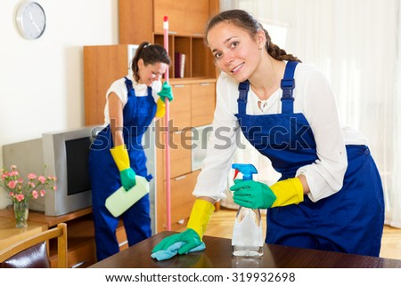 Happy adult female workers cleaning company ready to start work - stock photo