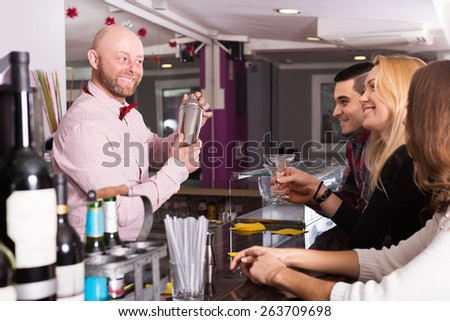 Happy adult friends drinking and chatting with smiling barman at bar counter - stock photo