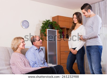 Happy adult man showing his future wife to smiling parents