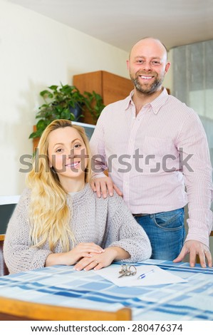 Happy adult married couple sitting at table with keys and documents - stock photo
