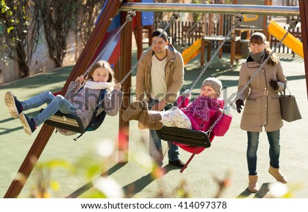 Happy adult parents watching little daughters swinging at playground. Focus on blonde girl - stock photo