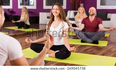 Happy adult people studying new position at yoga school - stock photo