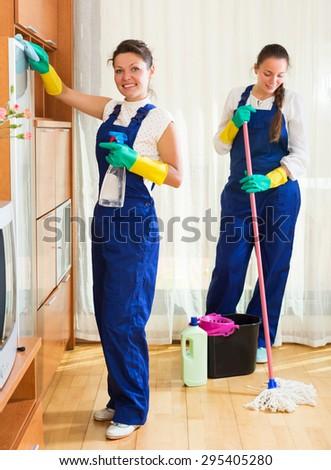Happy adult professional cleaners washing apartment with rag and mop