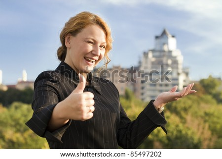 happy adult redhead business woman broker shows real estate - stock photo