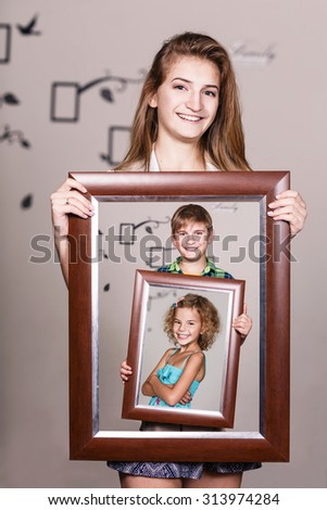 Happy adult sister holding portrait with her family each is located inside their own frame  - stock photo