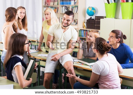 Happy adult students during break in classroom interior
