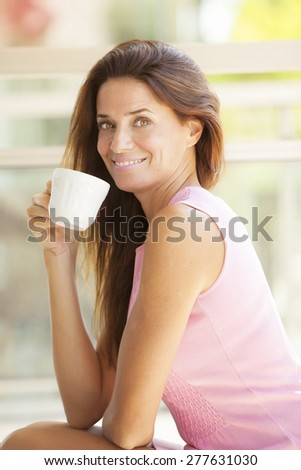 Happy adult woman having tea outdoors - stock photo