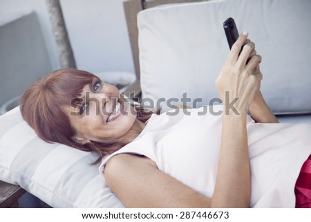 Happy adult woman with mobile phone, sending text message