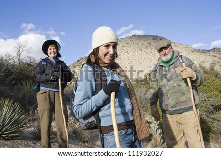 Happy adult woman with parents on hiking trip