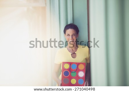Happy adult woman with shopping bag smiling outdoors - stock photo