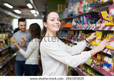 Happy adults choosing tinned food at supermarket - stock photo