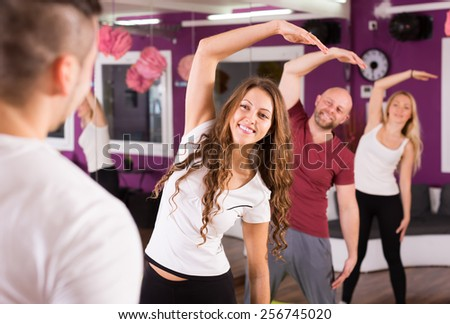 Happy adults having group fitness class in sport club - stock photo