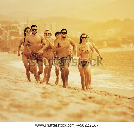 Happy adults running at sandy beach in summer day
